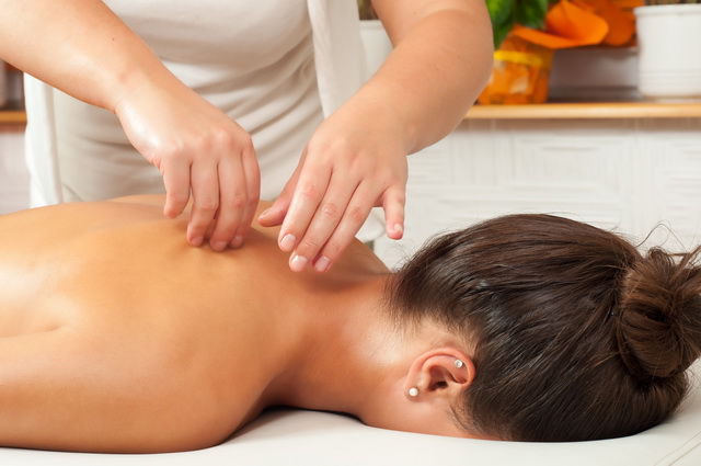 Female lying facing downwards while massage therapist is massaging her shoulders - ACMM